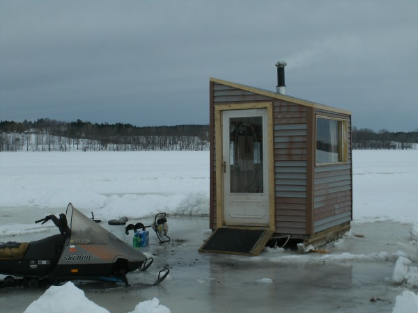 &quotThe Lakehouse&quot that Ron Ingals of Hermon built is mostly scavenged materials supplemented with $150 worth of purchased items. It features a large picture window, a spice cabinet (Ron likes to cook) a wood stove and home sewn curtains to name a few. All told, ice auger and snowmobile included, his investment is $250. Ron has three kids, so frugality is not an option, it is a requirement, he says.
