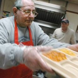 Dennis Plourde of Bangor serves a tray of food Wednesday at The Salvation Army on South Park Street in Bangor. Plourde, who is developmentally disabled, is a participant in the Downeast Horizons day program.
