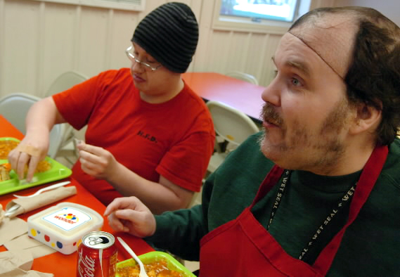 "After preparing and serving lunch at The Salvation Army in Bangor, Kenneth Pelkey of Howland and Herbert Skidgel of Bangor sit down to enjoy their own lunch Wednesday. Both Pelkey and Skidgel are developmentally disabled and participants in the Downeast Horizons day program. ""The more you help people, the more they feel good inside,"" said Skidgel of the volunteer work Downeast Horizon clients do on a monthly basis by planning, serving and cleaning up at The Salvation Army."