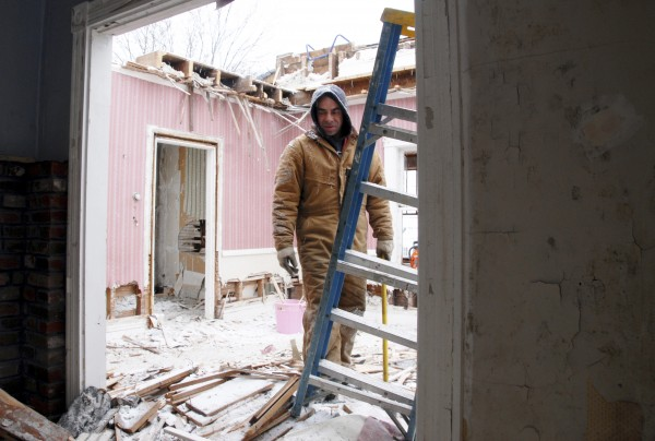 Millinocket contractor Grant Boynton reaches for a ladder while working on the demolition of a Lincoln Street house in Millinocket on Thursday.