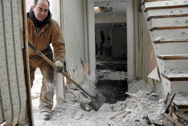 Millinocket contractor Grant Boynton shovels snow and cellulose while working on the demolition of a Lincoln Street house in Millinocket on Thursday.