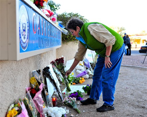 Rosey Koberlein of Tucson leaves flowers outside the office of U.S. Rep. Gabrielle Giffords, D-Ariz. in Tucson, Ariz. on Saturday, Jan. 8, 2011 after Giffords and others were shot outside a Safeway grocery store as she was meeting constituents.