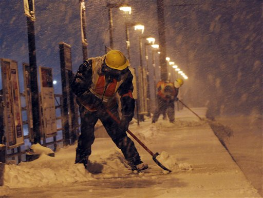 Workers clear a platform at the Edison train station as snow falls during a storm late Wednesday, Jan. 26, 2011 in Edison, N.J.