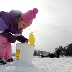 "Mikayla McMullen, 8, of Orrington, examines the ice fishing bait during the first of several winter camping days at Camp CaPella in Lucerne on Saturday. Mikayla attends Camp Capella, which is located on Phillips Lake and devoted to both children and adults with developmental disabilities in the summer, but this is her first time winter camping. ""I love it here,"" she said."