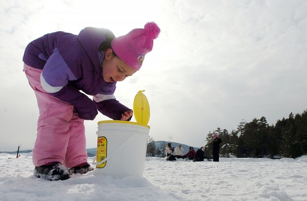 Mikayla McMullen, 8, of Orrington, examines the ice fishing bait during the first of several winter camping days at Camp CaPella in Lucerne on Saturday. Mikayla attends Camp Capella, which is located on Phillips Lake and devoted to both children and adults with developmental disabilities in the summer, but this is her first time winter camping. &quotI love it here,&quot she said.