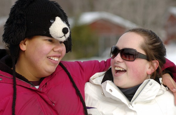 Geneva Langevin of Bucksport shares a laugh with camp counselor Sarah Poitras of New Market, NH, during Camp CaPella's first winter camping day on Saturday. Nine campers attended the event, which was designed for childrens age 5 to 13 years old with developmental disabilities and featured snow painting, snowmobile rides, and ice fishing, which was Geneva's favorite activity of the day.