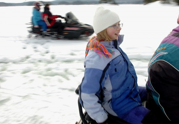 Sarah McInley, 12,  of Orland, braces herself as she takes off on a snowmobile ride on Phillips Lake in Lucerne on Saturday. Sarah was participating in the first of several winter camping days at Camp CaPella, which serves developmentally challenged children and adults.