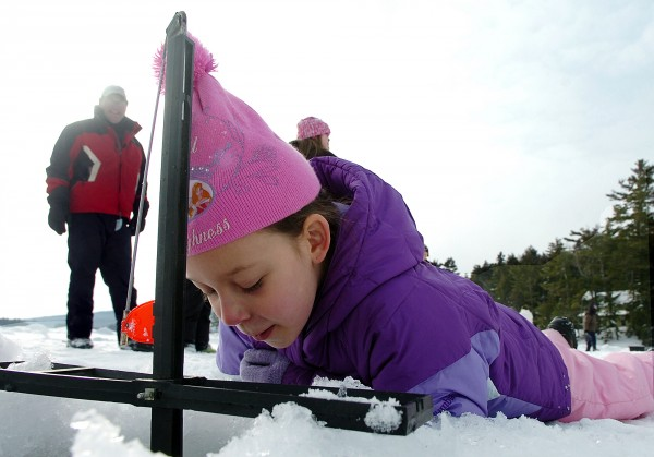 Mikayla McMullen, 8, of Orrington, examines the ice fishing trap during the first of several winter camping days at Camp CaPella in Lucerne on Saturday. Mikayla attends Camp CaPella in the summer, which is located on Phillips Lake and devoted to both children and adults with developmental disabilities, but this is her first time winter camping. &quotI love it here,&quot she said.