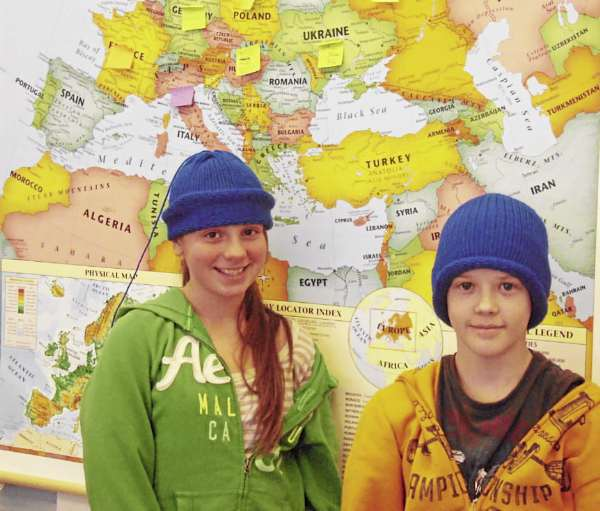 Maddy Postell and Kyle Kilcollins model two of the 90 hats knitted by five volunteers for Presque Isle Middle School seventh graders to wear to the World Cup Biathlon Championships at the Nordic Heritage Center Friday. The map in teacher ElaineHendrickson's social studies and English classroom shows what countries the visiting biathletes represent.