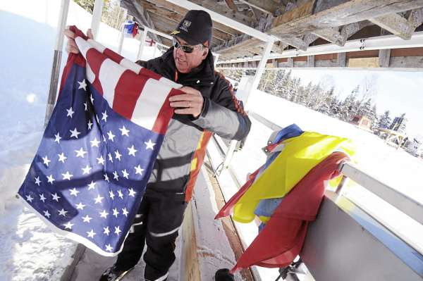John McCrea of Fort Fairfield helps fellow volunteers fold the U.S. flag and other national flags Thursday afternoon, Feb. 3, 2011 after taking them off flag poles behind the  biathlon target range at the Nordic Heritage Center. The flags were later brought to the University of Maine at Presque Isle to be paraded by the national teams during Thursday evening's  opening ceremony there.