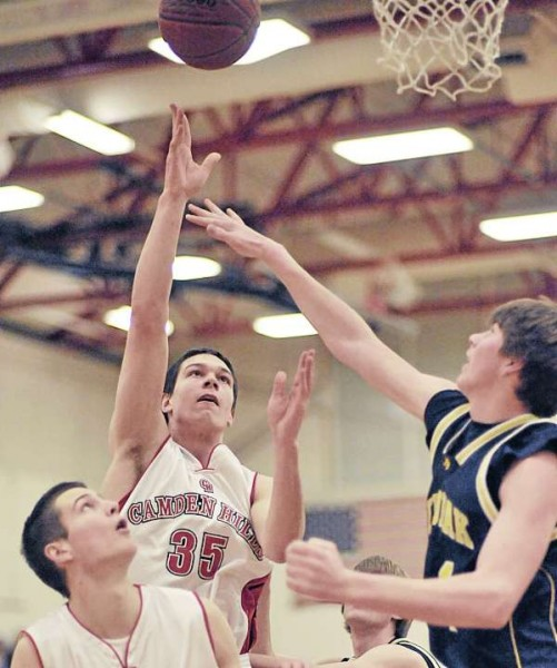 Camden Hills' Tyler McFarland (35) puts up a shot over teammate Keegan Pieri, (bottom), and Medomak Valley's Isaac Durkee (24) in the first half of their game in Camden Friday , Feb. 5, 2011.