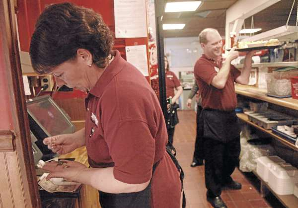 "Ramona Corbin counts out her tips during the lunch rush at Governor's Restaurant in Bangor on Friday. Employed at Governor's for 29 years, Corbin says, ""I'm an independent contractor who just happens to work at Governor's. The customers are my employers."""