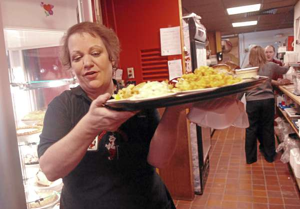 Waitress Carolyn Fish balances a tray of food during the lunch rush at Governor's Restaurant in Bangor on Friday. A recent bill proposed to the Maine Legislature seeks to revise the current law regarding individual service employees keeping their own tips.