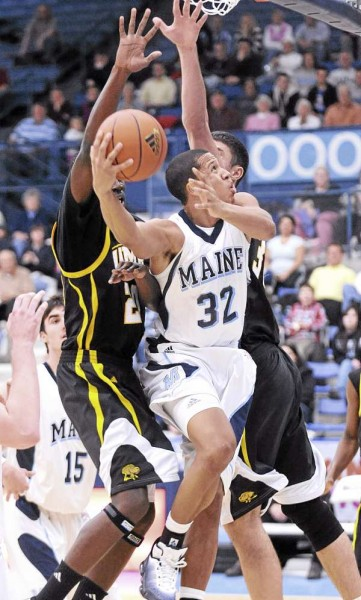 The University of Maine's Gerald McLemore (32) drives to the basket between UMBC's Adrian Sachell (left) and Justin Fry during the second half of the game in Orono Sunday afternoon.