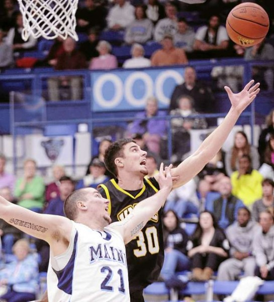 The University of Maine's Sean McNally (21) and UMBC's Justin Fry go up for a rebound during the first half of the game in Orono Sunday afternoon.