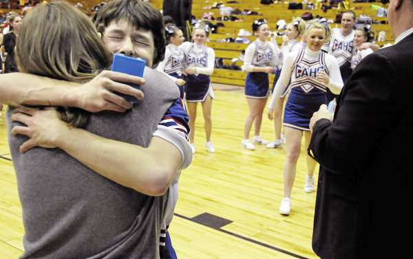 Colby Endy gives assistant coach Janice Mosher, left,  a hug as he and his Panther teammates pick up their first place medals in the Maine High School Class D Cheerleading Competition at the Bangor Auditorium Saturday afternoon, Feb. 12, 2011. The Central Aroostook Panthers took first place.