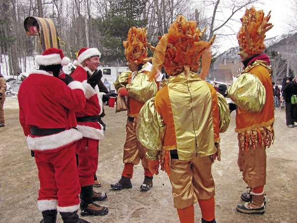 "Members of two toboggan teams — the ""Grandma Got Run Over By More Than a Reindeer"" team in Santa suits and the ""Royal Dutch National Toboggan Team"" in orange and gold — talk on Sunday during a break at the U.S. National Toboggan Championships in Camden."