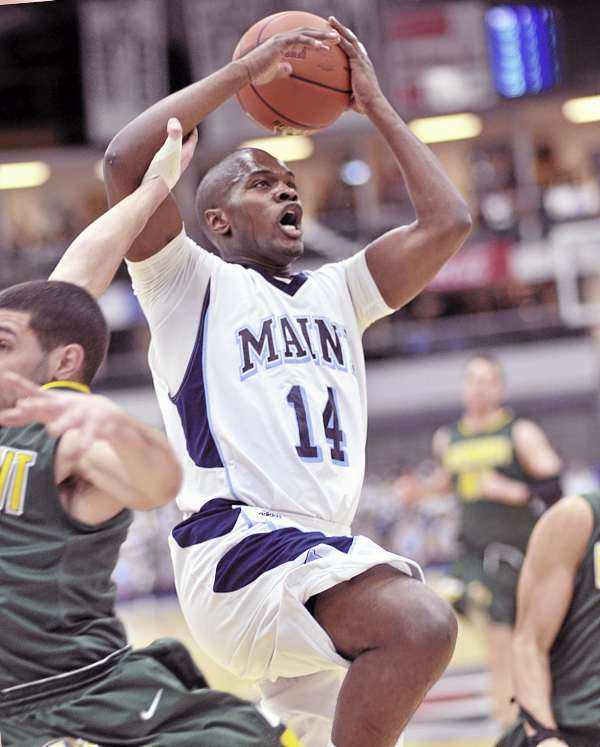 As Terrance Mitchell (14) of the University of Maine drives to the basket, he is fouled by Vermont's Joey Accaoui in the first half of Wednesday night's men's basketball game at Alfond Arena in Orono. Vermont won 73-57.