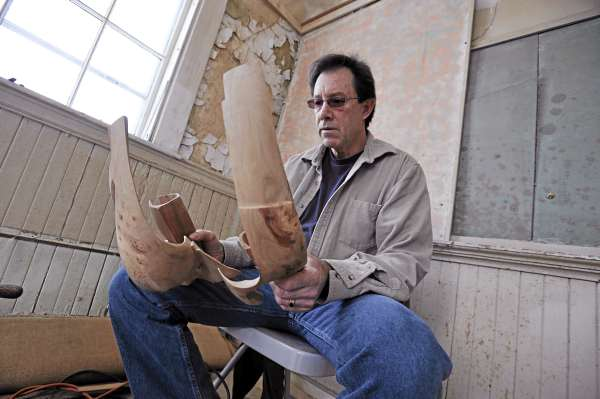 At his Bangor studio, artist Randy Colbath inspects two pieces of apple wood Feb. 17, 2011, that he has intricately carved over the past month  into a geometric sculpture.