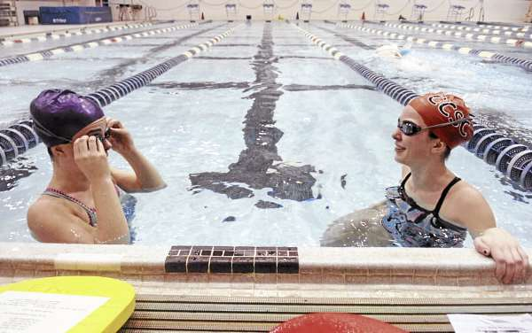 Veronica Wallace-Ewing, left, adjusts her googles as her twin sister, Ruby Wallace-Ewing, right, stretches during swim practice at the University of Maine's Wallace Pool on Thursday, February 27, 2011. The Orono seniors will be swimming this weekend in the Maine Principals Associations championship meet this weekend. Due to concerns about water and air quality, the MPA has issued new attendence guidlines for the event.