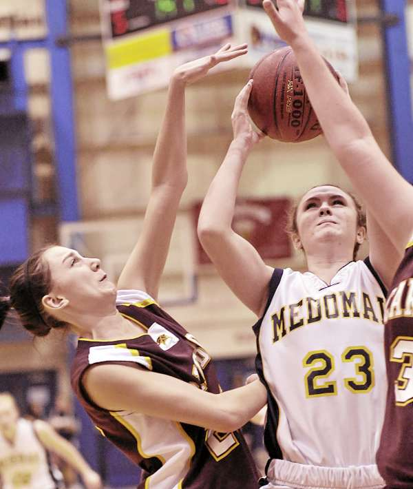 Caribou's Rebecca MacDougal, left, tries to get just the ball as she blocks Medomak's Roxanne Jelenfy (23) in the first half of their game at the Bangor Auditorium Friday, Feb. 18, 2011. Medomak advanced 52-30.