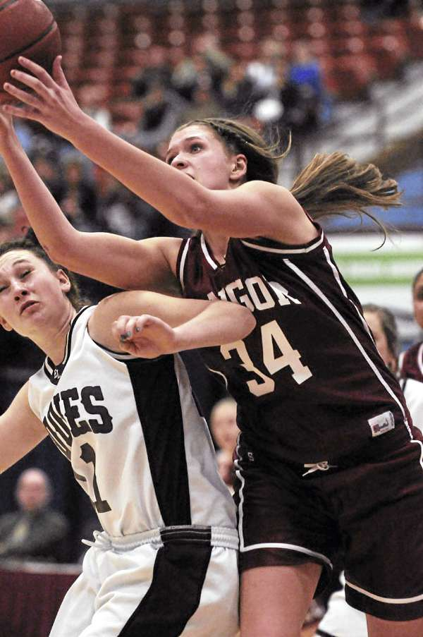 Bangor's Kristen Henigan reaches over the shoulder of Edward Little's Francesca Lally during second half-action on Friday, Feb. 18, 2011 at Augusta, Edward Little won 74-56.