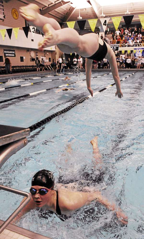 Bangor's Jamie Hunsaker touches the side of the pool as Jenny Dickson leaps off the platform as the pair complete in the 400 yard freestyle relays at Bowdoin college during the Class A swimming and diving championship on Monday, February 21, 2011. the pair along with Meri Wicks and Emma Waddell won the event and sealed Bangor meet victory.