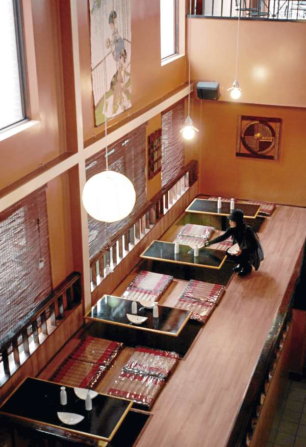 Wirawan Vivul decorates the Japanese-style sitting area in Zen, a new Asian fusion restaurant located on Main Street in Bangor.