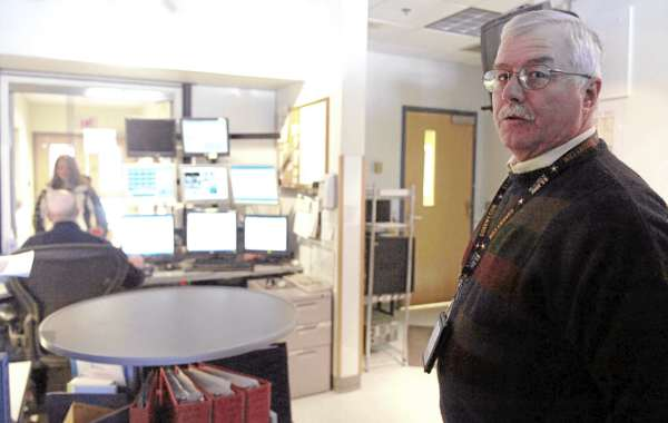 Lt. Paul Paradis (right) of the University of Maine Police Department, in the communications center of the department's Orono campus headquarters on Tuesday, February 22, 2011. The department, along with the police departments of Old Town and Orono, is in the process of undergoing a rigorous professional accreditation.