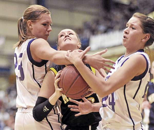 John Bapst's Taylor Edgecomb (23) and Brittany Williams (24) try to stop Medomak's Lindsay Ranquist (12) in the second half of their game Wednesday Feb. 22, 2011 in Bangor.