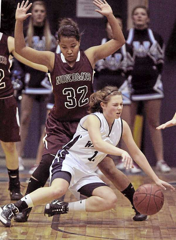 Presque Isle's Chandler Guertte (14) loses her footing  while being guarded by  Nokomis' Juliane Smith (32)  in the second half of their game at the Bangor  Auditorium Wednesday Feb. 23, 2011.