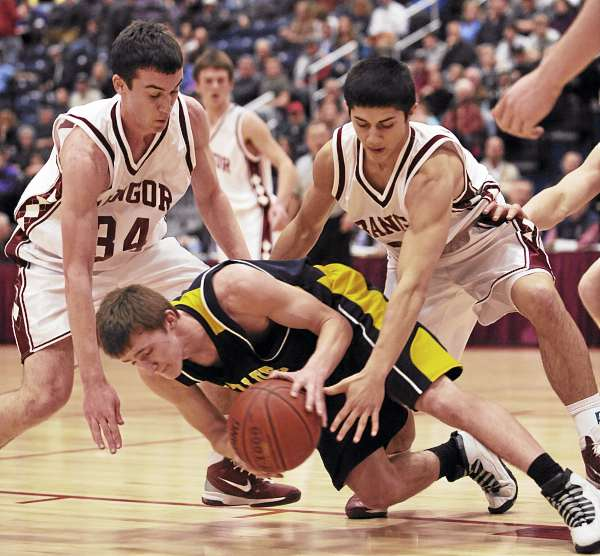 Bangor's Sean Mackintosh, left, and Nick Sherwood, right, look to strip the ball from Mt Blue's Eric Berry as he goes down during first period action on Wednesday, February 23, 2011 during Class A semifinal action at the Augusta Civic Center. Bangor won.