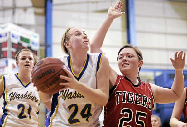 Washburn's Rebecca Campbell (24) drives to the basket with pressure from Fort Fairfield's Danielle Tracy (25)  during their Class D East girls semifinal at Bangor Auditorium Thursday afternoon, Feb. 24, 2011. On the left is Washburn teammate Sarah Sjoberg (21).