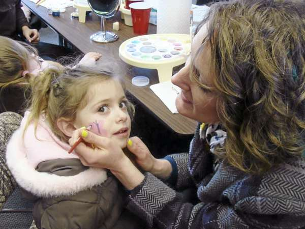Nina Kvaracein, 3, of Shrewsburg, Mass. had Tara Heffner, a volunteer at Family Fun Day in Greenville, paint a butterfly on her face Thursday. Her sister Laila, 20 months old, in the background, also got her face painted during the free event. The family, who have a camp on Moosehead Lake, enjoyed the free festivities while vacationing.