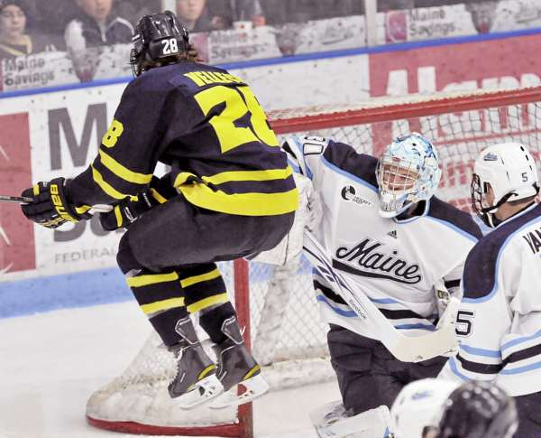 Merrimack's Jeff Velleca (28) jumps to distract Maine goalie Dan Sullivan (30) after a shot in the third period of their college hockey game, Friday Feb. 25, 2011, in Orono, Maine.