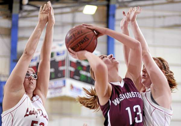 Washington Academy's Taylor Seeley puts a shot through the defense of Central's Bekah Campbell, left, and Roberta Trafton, right,   during their Class C East girls semifinal at Bangor Auditorium Friday afternoon, Feb. 25, 2011.