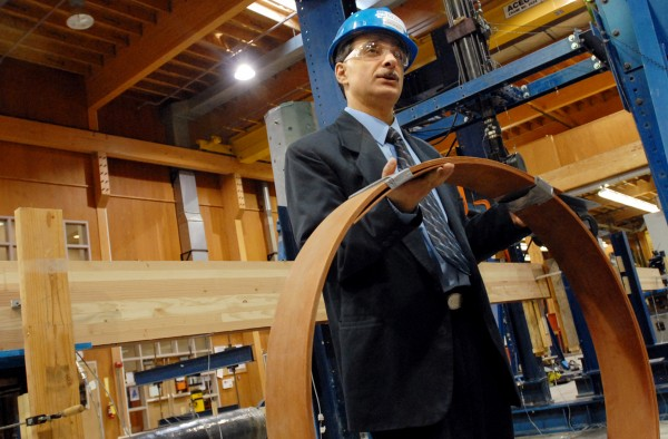 The University of Maine's AEWC Advanced Structures and Composites Center has been issued a patent for coming up with a method of prestressing glued-laminated timber beams to strengthen the wood for use in construction.  Habib Dagher, director of the Advanced Structures and Composites Center, holds a roll of the glass fiber reinforced polymer (GFRC) that is bonded to the tension side of a beam, increasing the beam's strength by 38%. Dagher and Associate Professor of civil engineering Mac Gray are the lead inventors on the patent.