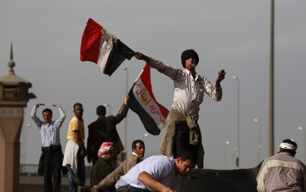 An anti-government protester swings an Egyptian flag to beckon others to reinforce those at the front line of clashes with pro-government supporters near the Egyptian Museum in downtown Cairo, Egypt, Thursday, Feb. 3, 2011. Protesters and regime supporters skirmished in a second day of rock-throwing battles at a central Cairo square while new lawlessness spread around the city.