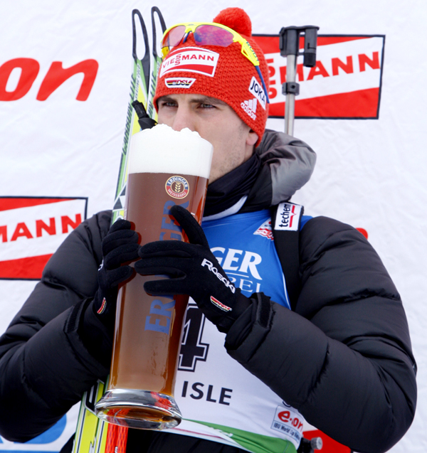 Arnd Peiffer, of Germany, sips from an Erdinger mug, on the medal stand after winning the men's 10 kilometer sprint at the Biathlon World Cup, Friday, Feb. 4 in Presque Isle, Maine.