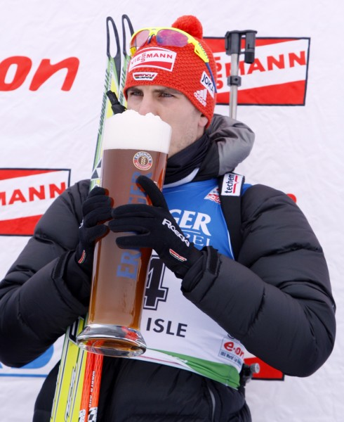 Arnd Peiffer, of Germany, sips a beer on the medal stand after winning the men's 10 kilometer sprint at the Biathlon World Cup, Friday, Feb. 4, 2011, in Presque Isle.