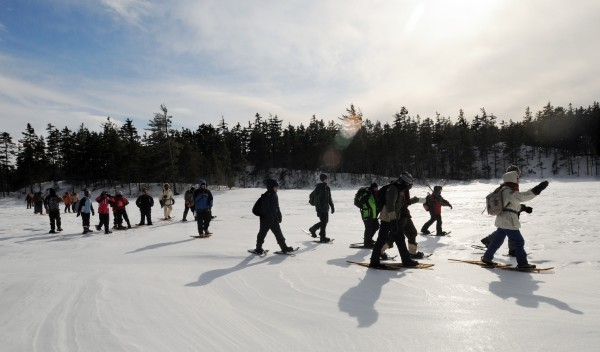 A group of teenagers snowshoe over the ice of Midday Pond during their hike in the Borestone Mountain Sanctuary Sunday.  The students - who participate in the Lifejackets program - learned about winter skills such as building a fire on the snow and making a lean-to.