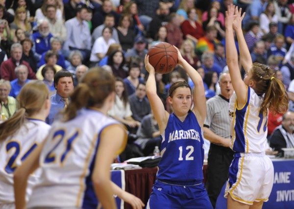 Deer Isle-Stonington's Heidi Brewer (12) looks to pass as Washburn's Carmen Bragg (right) tries to block it during their Class D Eastern Maine Class D girls basketball final Saturday at the Bangor Auditorium. Washburn won 50-43.