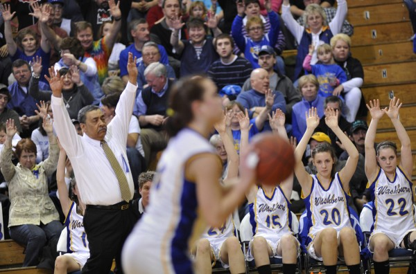 Washburn coach Mike Carlos and his players hold up their hands in support while a player shoots a free throw in their Eastern Maine Class D final against Deer Isle-Stonington Saturday.