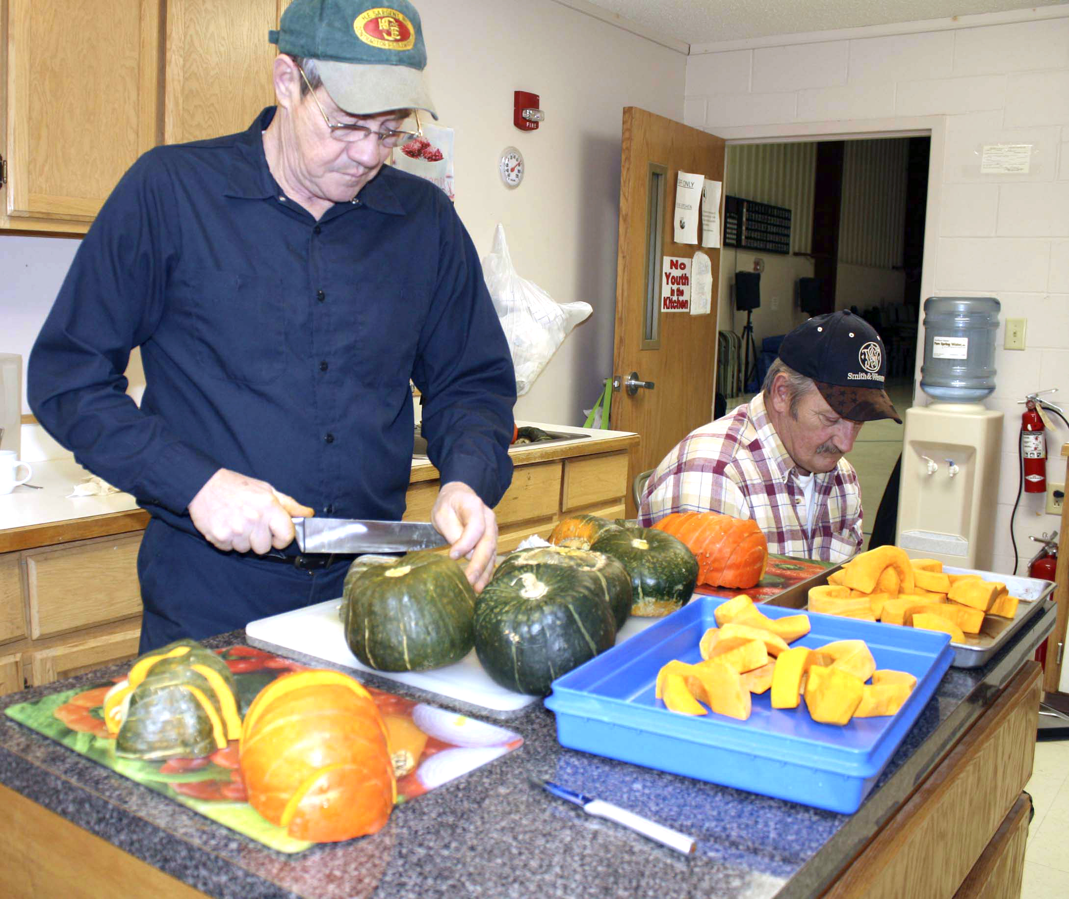 Dale Flewelling (left) and Eugene Stewart cut, peel, seed and prepare winter squash for commercial sale to support Friends of Aroostook's nonprofit free fresh produce programs.