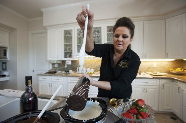 Shari Fitzpatrick drizzles white chocolate onto a dark chocolate-dipped bottle of wine in her home kitchen in Placerville, Calif., recently.