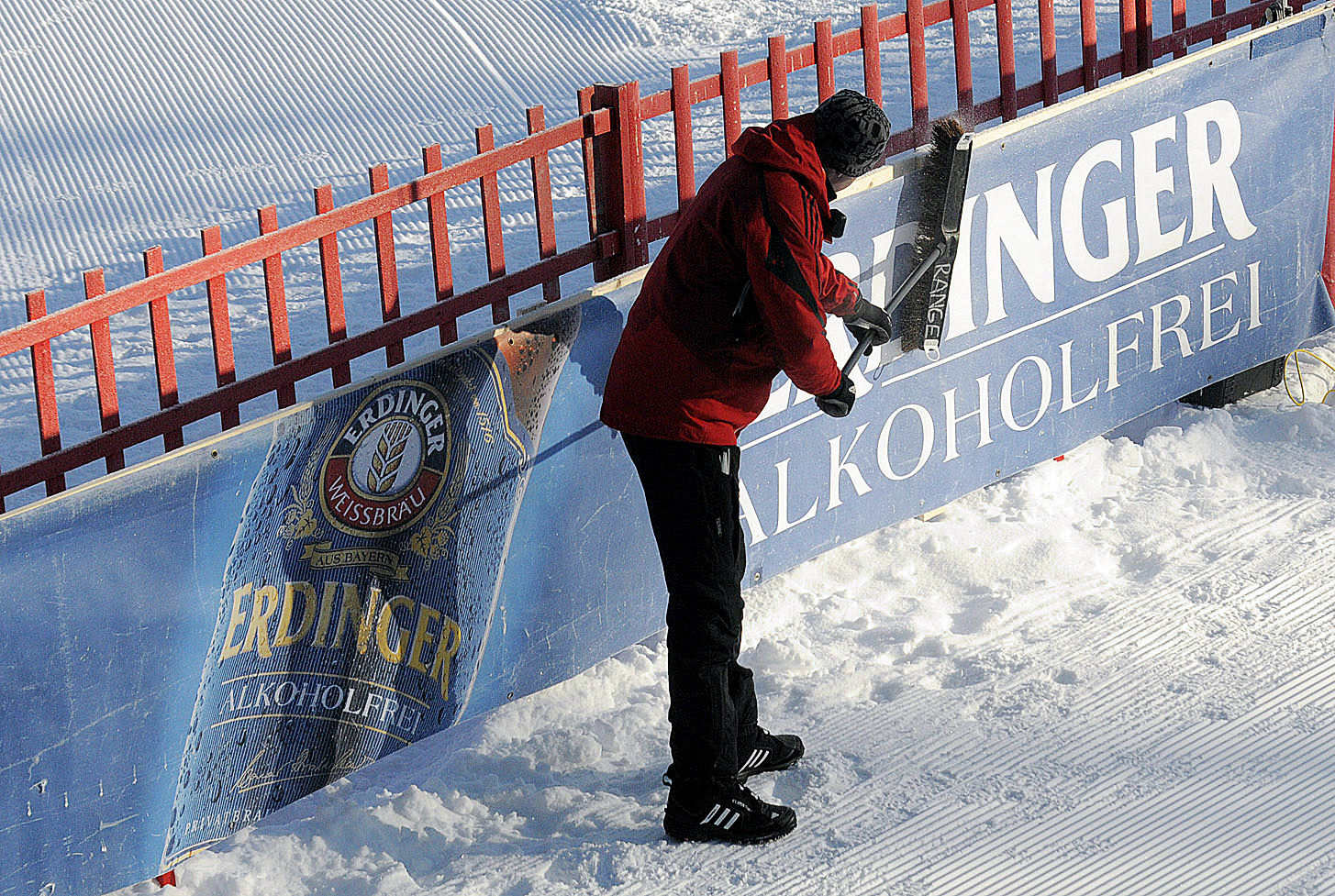 A volunteer cleans the frost from an Erdinger advertisement at the 10th Mountain Ski Center in Fort Kent on Thrusday morning.