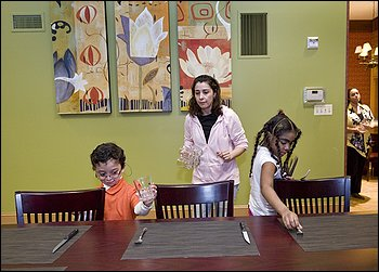 Benjamin Lopez and Jesibeth Rodriguez help Benjamin's mother, Alejandra Lorca, set the table at Woodmont House, part of Children's Inn. Woodmont is for patients who don't need intensive services.