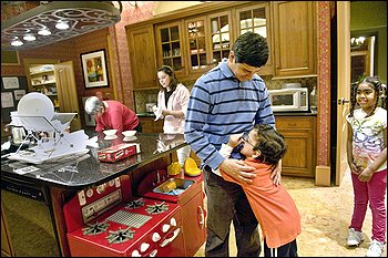 Benjamin Lopez and his father, Cristian, fool around at Woodmont House near the NIH in Bethesda while Ada Ivette Polo Vega, left, and Alejandra Lorca, Benjamin's mother, prepare dinner. Jesibeth Rodriguez, right, also lives in the house.