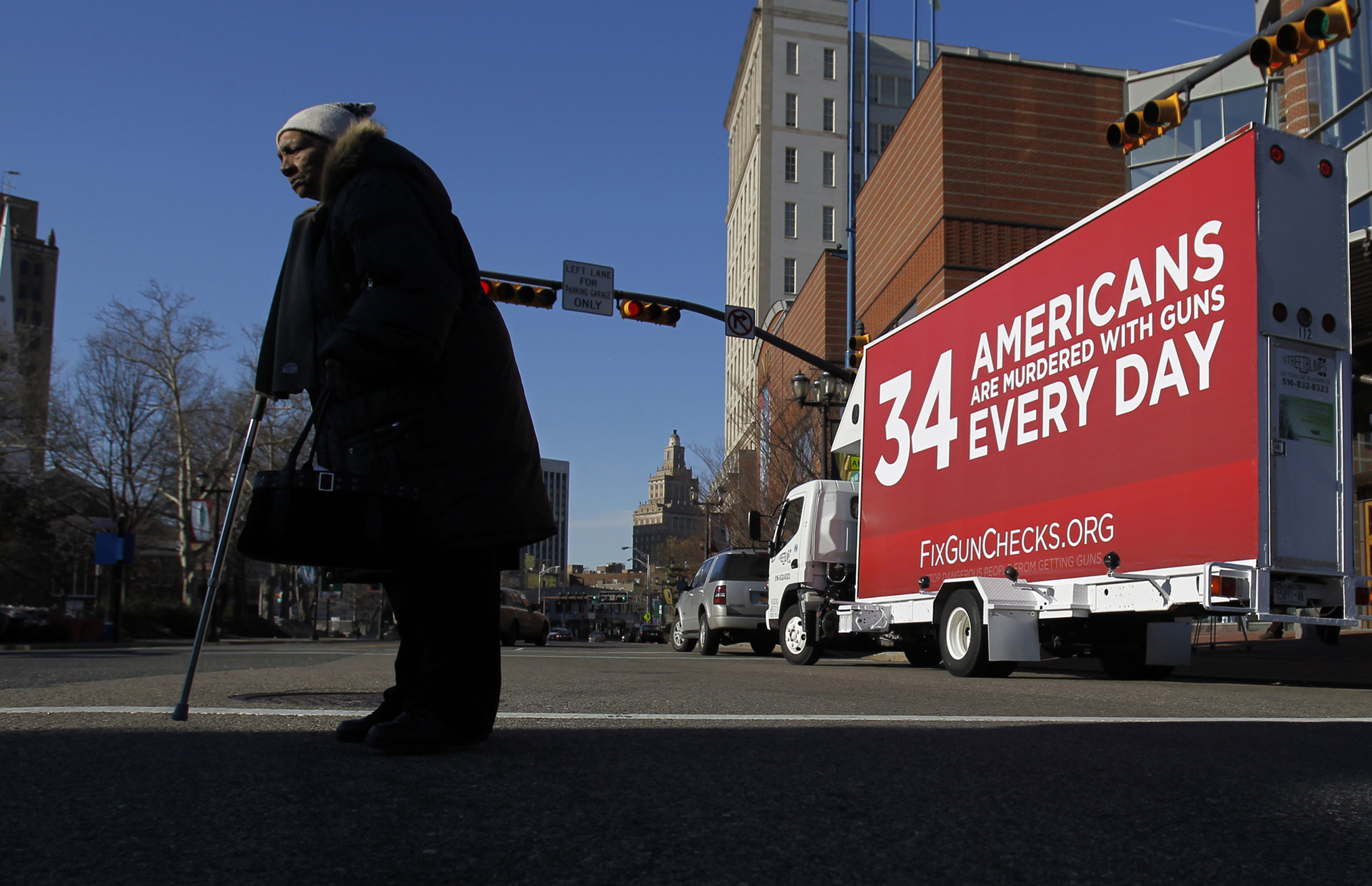A pedestrian crosses the street near a mobile billboard promoting the FixGunChecks.org Truck tour Wednesday, Feb. 16, 2011, in Newark, N.J. The truck will be driven across the nation as part of the Mayors Against Illegal Guns which was launched by New York City Mayor Michael R. Bloomberg on Wednesday. Its purpose will be to draw public attention to the deadly problems in the nationâ??s gun background check system.