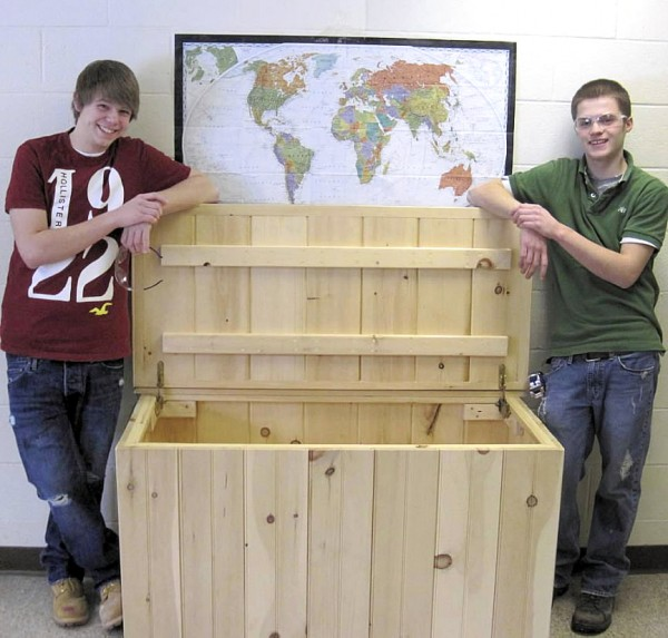 Kyle Wickstrom (left) and Brandon Adams, students in the residential carpentry program at the Caribou Technology Center, display the toy box they recently constructed and donated to the Hope & Justice Project.